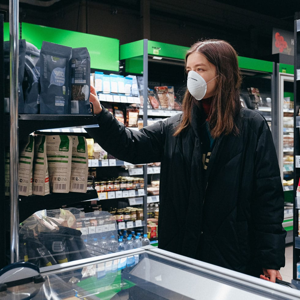 A woman wearing a surgical mask shopping groceries