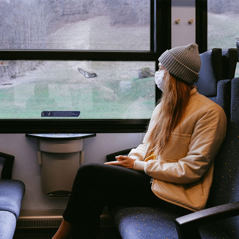 A woman wearing a surgical mask sitting in a train, looking outside the window.