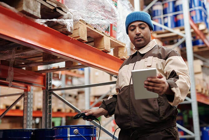 A warehouse worker looking at a tablet PC, showing the importance of data for resilient supply chains